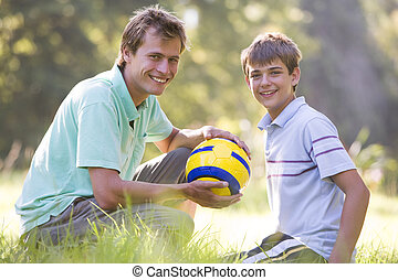 Man and young boy outdoors with soccer ball smiling