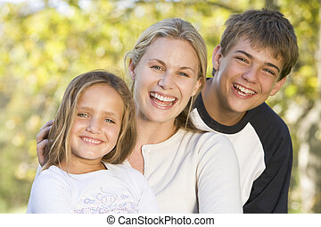 Woman with two young children outdoors smiling
