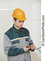 Electrician at cabling work - electrician worker in uniform...