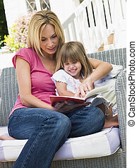 Woman and young girl sitting on patio reading book smiling