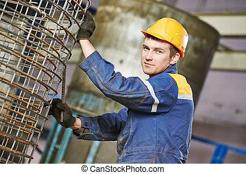 worker making reinforcement for pipe - industrial worker...