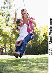 Woman and young girl outdoors on tree swing smiling
