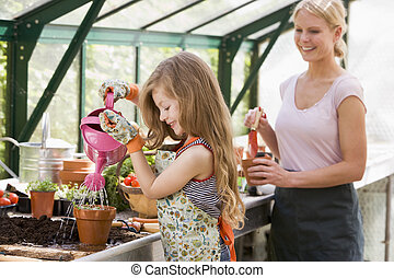Young girl in greenhouse watering plant with woman holding...