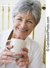 Woman in bedroom with coffee smiling