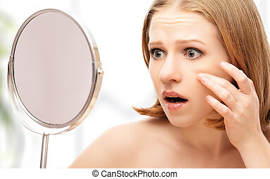 young beautiful healthy woman frightened saw in the mirror...