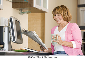 Woman in kitchen with newspaper and coffee smiling