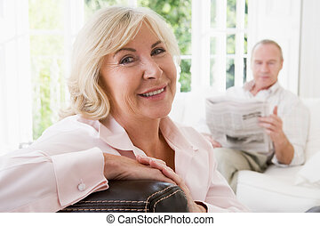 Woman in living room smiling with man in background reading...