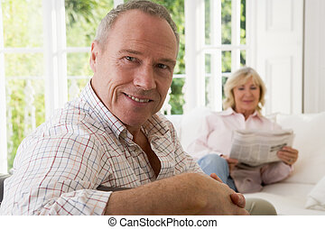 Man in living room smiling with woman in background reading...