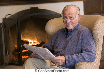Man sitting in living room by fireplace with newspaper...