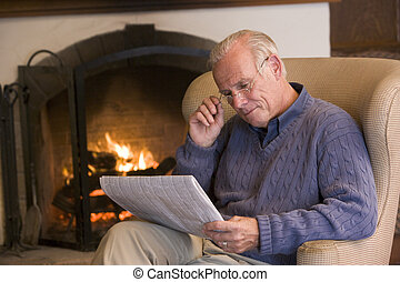 Man sitting in living room by fireplace with newspaper