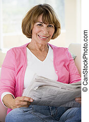 Woman relaxing with newspaper in living room and smiling