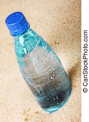 bottle of water on the hot sand - cold bottle of water on...