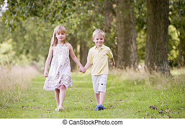 Two young children walking on path holding hands smiling