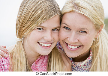 Mother and daughter at beach smiling