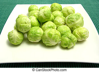 Brussels sprouts arranged on a white plate and green placemat