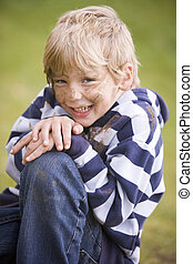 Young boy sitting outdoors dirty and smiling