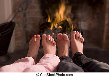 Children\\\'s feet warming at a fireplace