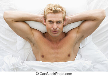 Man lying in bed relaxing
