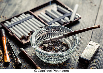 Glass ashtray with thin wooden pipes, cigarettes and lighter...