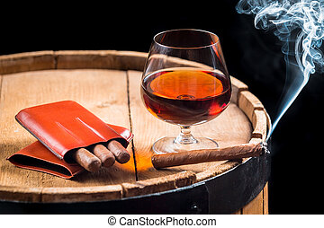 Cognac in a glass on barrel and burning cigar