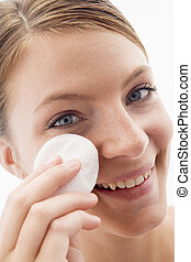 Woman removing makeup and smiling