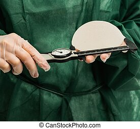 Plastic surgeon hands measuring silicon breast implants with...