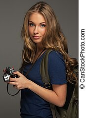 Positive young woman with long hair and blue eyes holding...