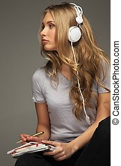 Young woman student with notebook listens to music