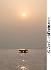 Sunset and boat silhouette, West Lake, Hangzhou, China -...