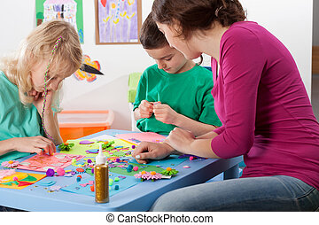 Creative games in kindergarden - Kids and a teacher playing...