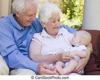 Grandparents outdoors on patio with baby smiling