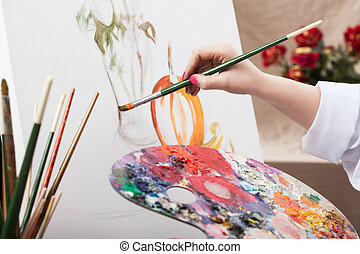 Artist painting a picture - A closeup of an artist with a...