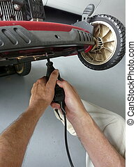 Sharpening Lawn Mower Blade - A man is sharpening the blade...