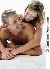 Couple lying in bed smiling - man and women on a bed...