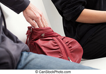 Slipping into a bag - A thief slipping his hand into a...