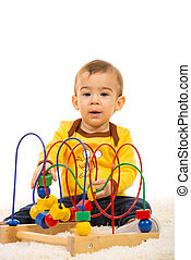 Toddler boy playing with wooden toy on carpet home
