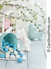 Basket of Easter Candy Eggs - A blue tin bucket tipped over,...