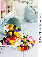 Colorful Jelly Beans - A blue tin bucket tipped over,...