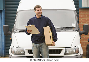 Deliveryperson standing with van holding clipboard and box...