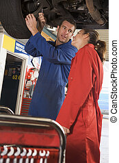 Two mechanics working under car smiling