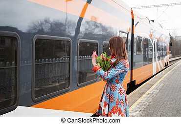 Woman with flowers salute to train passanger - Young woman...