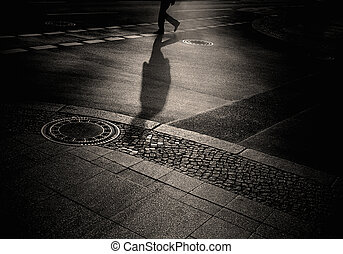 shadow of a person crossing a street in sepia black and...