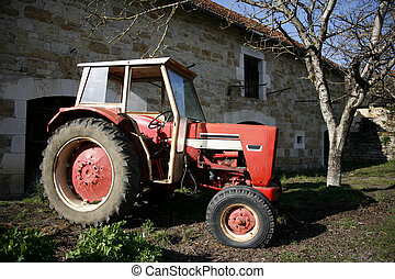 red tractor - Old red tractor in front of farm in Correze,...