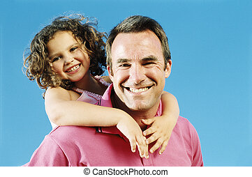 Father giving daughter piggyback ride outdoors smiling