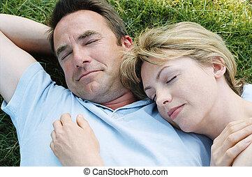 Couple lying outdoors sleeping