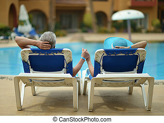 Elderly couple at pool - Back view of Elderly couple lying...