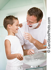 Man in bathroom putting shaving cream on young boy\\\'s nose