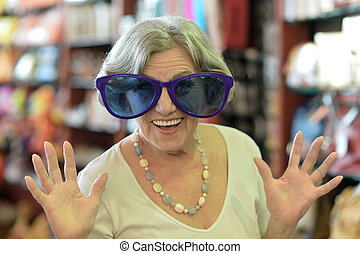 Senior woman in huge sunglasses at shopping mall