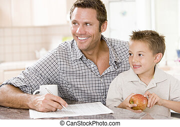 Man and young boy in kitchen with newspaper apple and coffee...