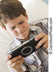 Young boy with handheld game indoors looking unhappy